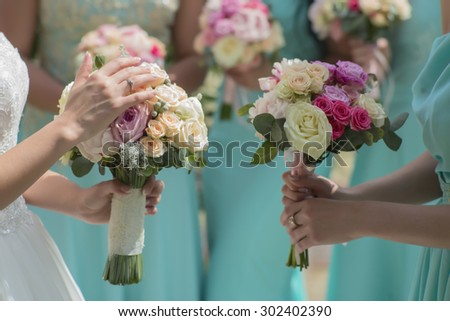 Few beautiful fresh wedding bunches of colorful rose flowers pink violet lilac purple white orange and yellow in hands of bride and bridesmaid in blue dresses, horizontal picutre