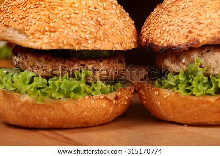 Few big delicious appetizing fresh burgers of green lettuce leaf cheese meat cutlet and white bread bun with sesame seeds closeup, horizontal picture - stock photo