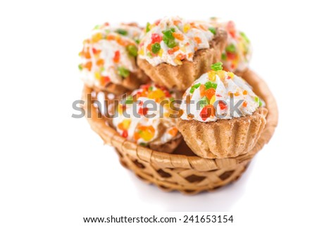 Few cakes in wicker basket on white table. - stock photo