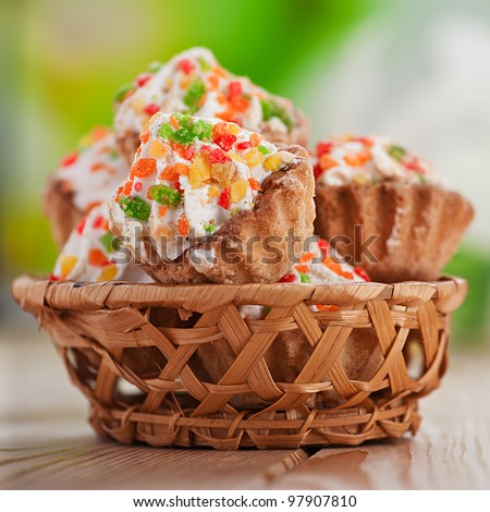 Few cakes in wicker basket on wooden table. - stock photo