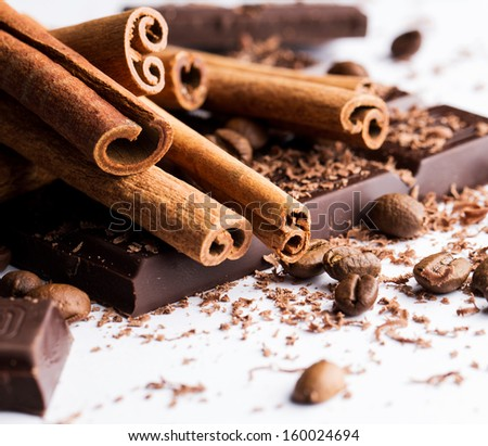 Few cinnamon sticks together with pieces of dark chocolate and some coffee beans on a white surface - stock photo