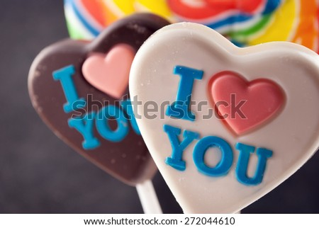 Few colorful lollipops and chocolate hearts against gray background. - stock photo