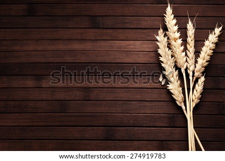 Few ears of wheat on a wooden background.