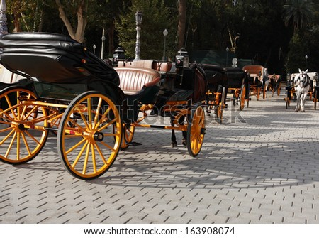 Few empty carriages with horses in park, Seville,Spain - stock photo