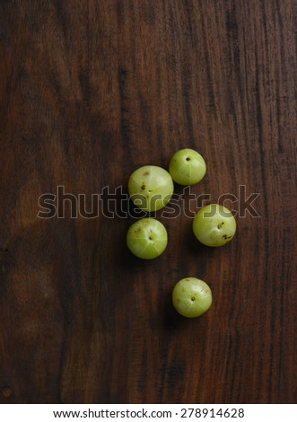 Few Indian gooseberries placed on wooden background. Top angle. - stock photo