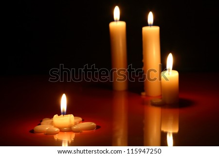 Few lighting candles on dark background with reflection