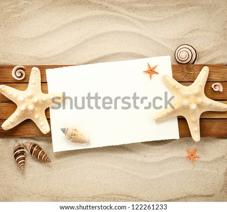 Few marine items on a wooden boards against sandy background.