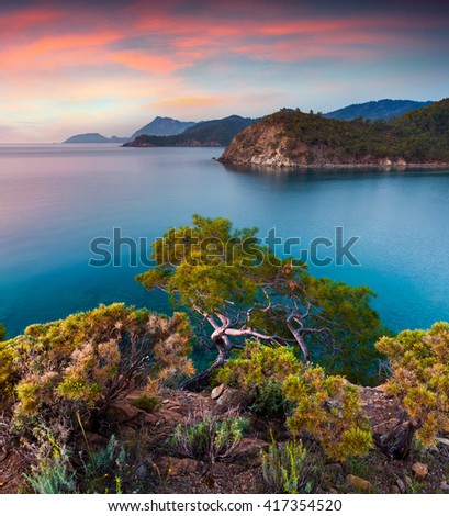 Few minutes before a sunrise on Mediterranean sea. Colorful sprind scene in the small bay near Tekirova village, District of Kemer, Antalya Province. Artistic style post processed photo. - stock photo