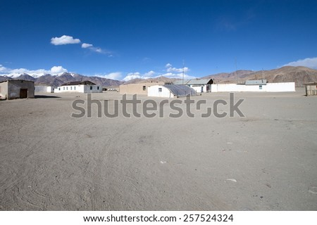 Few old houses, rocky mountains and scorched valley on a background of blue sky with a few white clouds. - stock photo