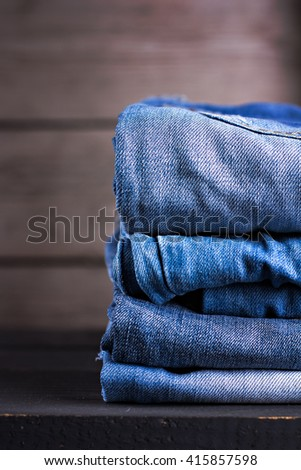 Few pair of jeans stacked on a wooden background - stock photo