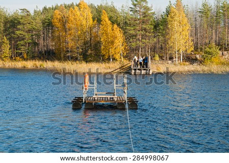 Few people waiting for the ferry to cross the lake in the Repovesi (Finland, South Karelia)