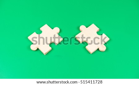 Few pieces of blank wooden puzzle. Isolated on green background. Slightly de-focused and close-up shot. Copy space.