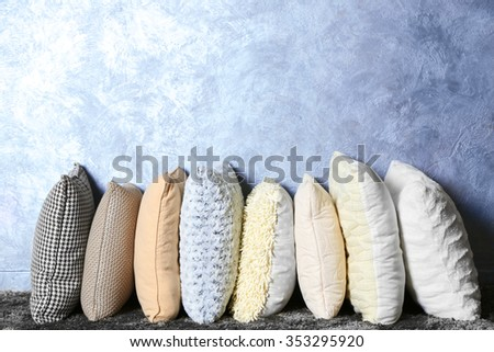 Few pillows on grey wall background - stock photo
