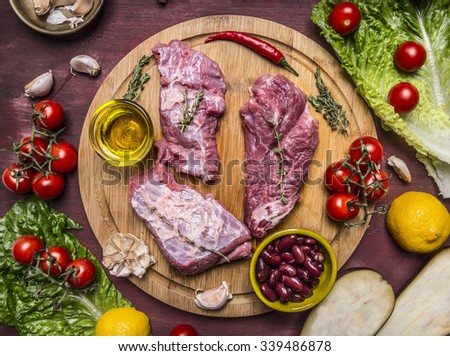 few slices of raw beef on a cutting board, around lie ingredients tomatoes on a branch, lemon, olive oil, red hot pepper, herbs, lettuce, eggplant on wooden rustic background top view - stock photo
