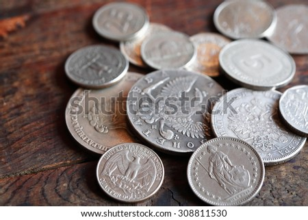 Few various coins of different countries on wooden background - stock photo