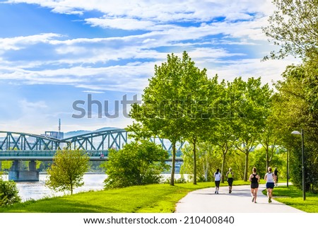 Few women running and cycling in beautiful green park alongside the river.Shot at Danube island,capital city of Austria - Vienna.The best place for sport activity and healthcare in this european town. - stock photo