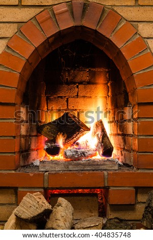 few wood and burnuing logs fire in fireplace in country cottage - stock photo