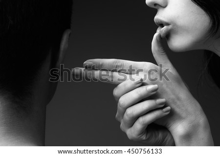 feyoung woman holding hands and fingers in gun gesture near lips shooting man on studio background, black and white
