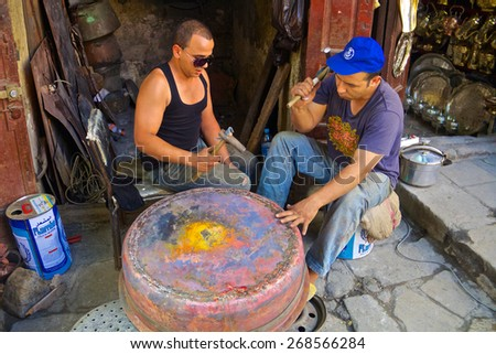 Fez, Morocco - May, 11 2013: Young moroccan men forging a copper pot in a souk in Fes Medina, Morocco - stock photo