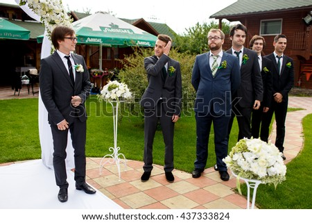 Fiance and groomsmen look funny stending in the line behind an altar