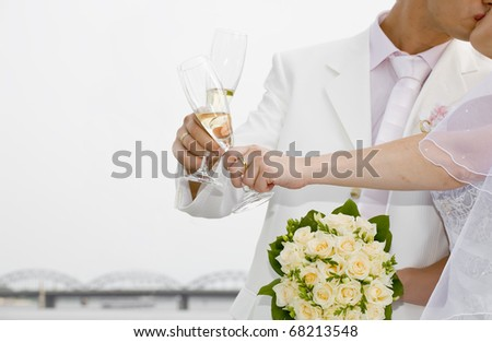 Fiance kiss the bride, holding glasses of champagne - stock photo