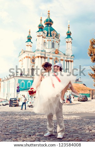 Fiancee and groom, sitting near a church - stock photo