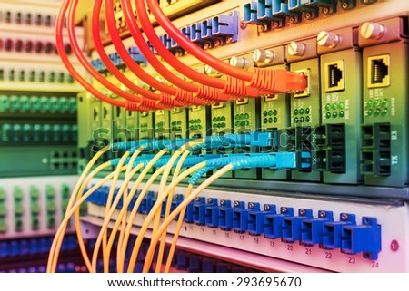 Fiber Optic cables connected to an optic ports and Network cables - stock photo