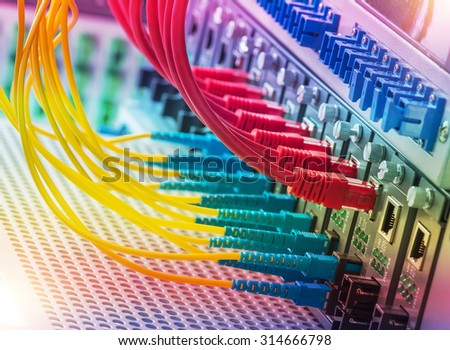 Fiber Optic cables connected to an optic ports and Network cables connected to ethernet ports. - stock photo
