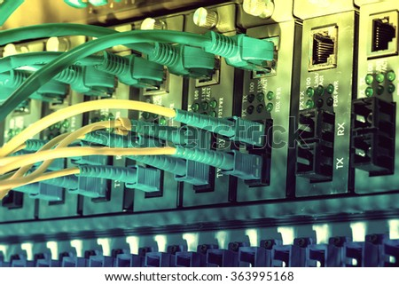 Fiber Optic cables connected to an optic ports and Network cables connected to ethernet ports - stock photo