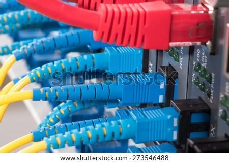 Fiber Optic cables connected to an optic ports and UTP Network cables connected to an Fast/Giga Ethernet ports - stock photo