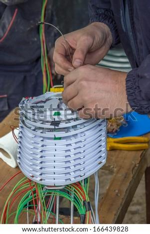 Fibre optic technician sorts optic cables in fiber splice cassettes, splice organiser tray.  - stock photo