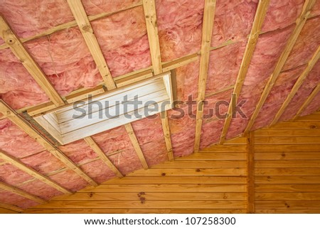 Fibreglass insulation installed in the sloping ceiling of a timber house. - stock photo