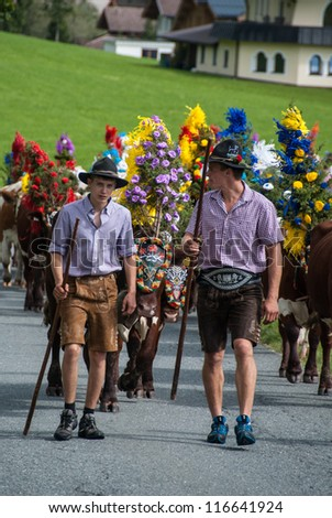 FIEBERBRUNN, AUSTRIA - SEPT 15: Two farmer boys at Traditional Almabtrieb. A ceremonial driving down of cattle from the mountain into valley in autumn in Fieberbrunn, Austria on September 15, 2012.