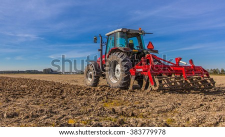 Field being ploughed by tractor under Blue Sky. Autumn Farming scene in the Netherlands,