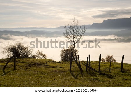 field fence with a gate, with mountains in the background, and the fog in the valley, on a cold morning - stock photo