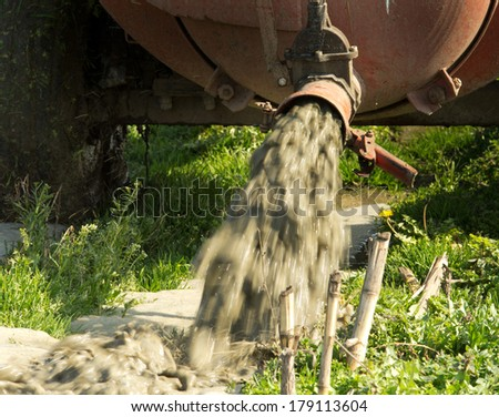 Field fertilizing with liquid manure from cistern - stock photo