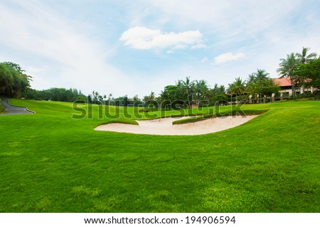 Field for a golf under the blue sky with white clouds