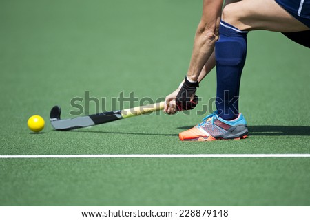 Field Hockey player, forcefully passing the ball to a tream mate - stock photo