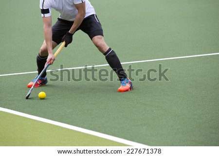 Field Hockey player, ready to pass the ball to a team mate - stock photo