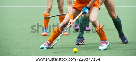 Field hockey players challenge eachother for possession of the ball on the midfield battle of a hockey mach - stock photo