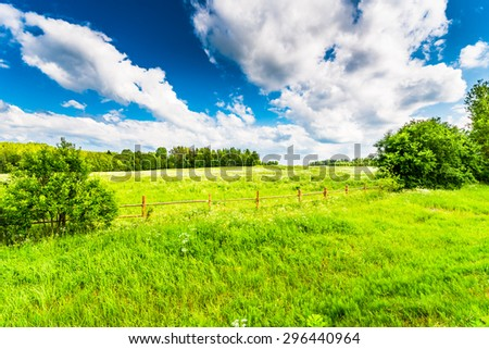 Field in the forest enclosed by a wooden fence on a background of the cloudy sky - stock photo