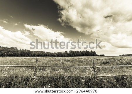 Field in the forest enclosed by a wooden fence on a background of the cloudy sky. Image in the yellow toning - stock photo