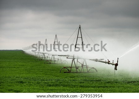 Field irrigation in agriculture. supply of water to the fields, lacking moisture and increase its reserves in the root zone of the soil to increase soil fertility - stock photo