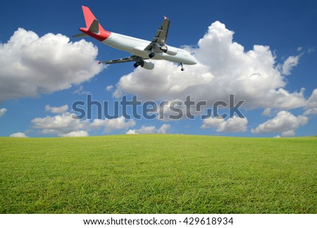 Field of green grass on blurred The plane was landing and sky-clouds background.