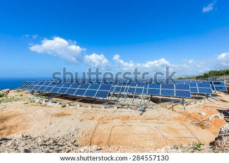 Field of solar collectors on rotatable metal construction with blue sky