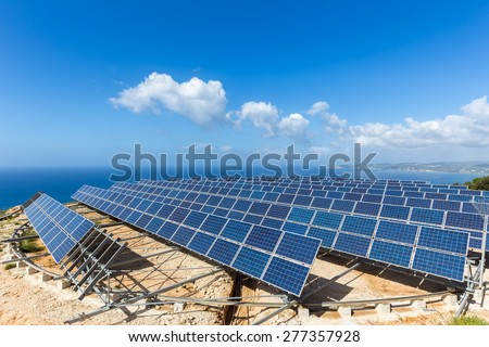 Field of solar panels or solar collectors at sea - stock photo