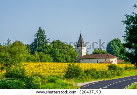 Field of sunflowers and church in France. - stock photo