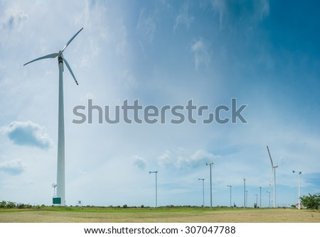Field of white wind turbines generating electricity on blue sky - stock photo