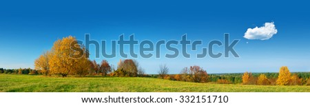 Field panorama on autumnal day with a single cloud in the sky - stock photo
