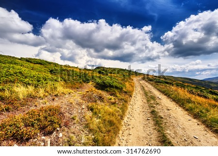 Field road in the mountains under the blue sky. Dramatic scene. Europe - stock photo